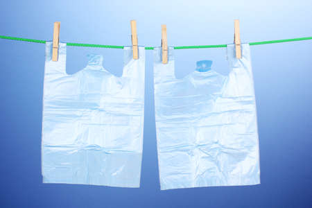 Cellophane bags hanging on rope on blue background Stock Photo - 14117194