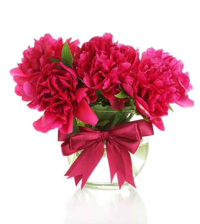 mooie roze pioenrozen in een glazen vaas met strik op wit wordt geïsoleerd