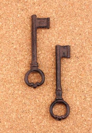 Two antique keys on cork background Stock Photo - 14117688