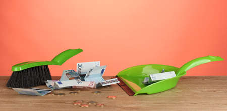 Sweeps money in the shovel on colorful background close-up photo