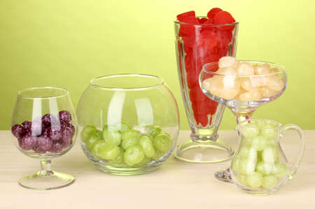 Color candies in glasses on wooden table on green background photo