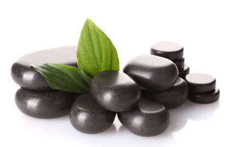 Spa stones and green leaves isolated on white photo
