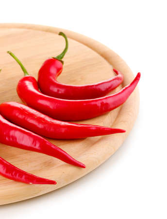 Red hot chili peppers on wooden plank isolated on white photo