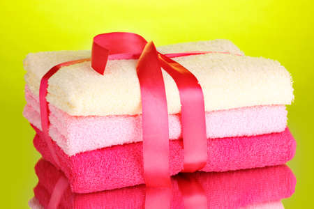 Colorful towels with ribbon on green background Stock Photo - 14116826