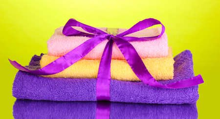 Colorful towels with ribbon on green background Stock Photo - 14117591