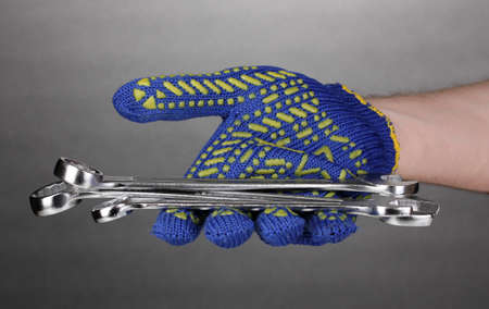 Wrenches in hand with protection glove on grey background photo