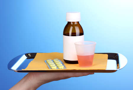Hand holding tray with medicines on blue background photo