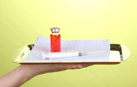 Hand holding tray with syringe and medicines on green background photo