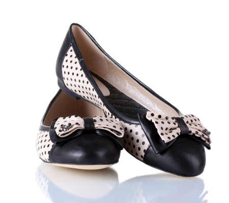 Female flat ballet shoes patterned with black polka dots isolated on white photo