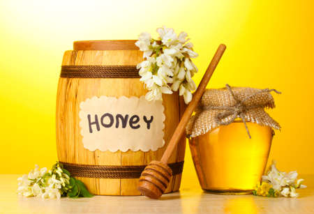 Sweet honey in barrel and jar with acacia flowers on wooden table on yellow background photo