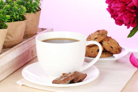 cup of coffee, cookies, chocolate and flowers on table in cafe photo