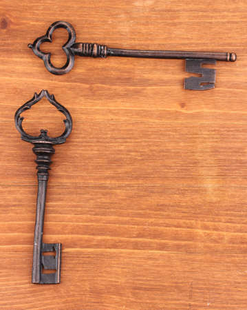 Two antique keys on wooden background Stock Photo - 14117597