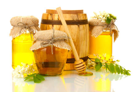 Sweet honey in barrel and jars with acacia flowers isolated on white photo