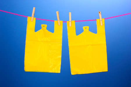 Cellophane bags hanging on rope on blue background photo