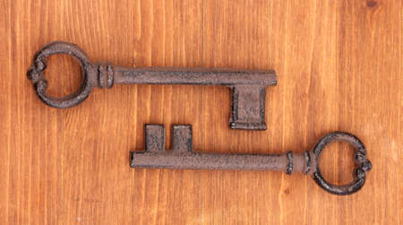 Two antique keys on wooden background photo