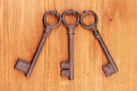 Three antique keys on wooden background photo