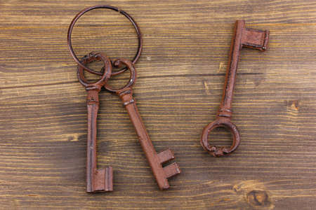 a bunch of antique keys on wooden background photo