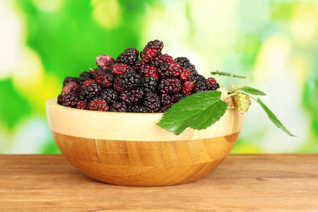 Wooden bowl with ripe mulberries on wooden table on bright green background close-up photo