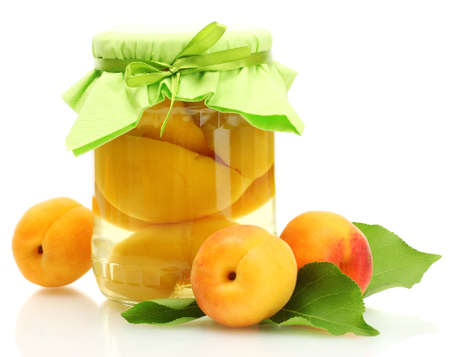canned apricots in a jar and sweet apricots isolated on white photo