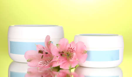 Jars of cream with flower on green background photo