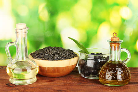 Olive and sunflower oil in the small decanters on green background close-up photo