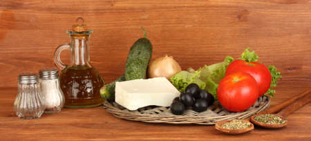 Ingredients for a Greek salad on wooden background close-up photo