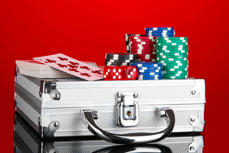 Poker set on a metallic case on bright red background photo