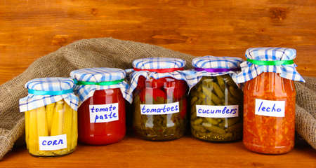 Jars with canned vegetables on green background close-up photo