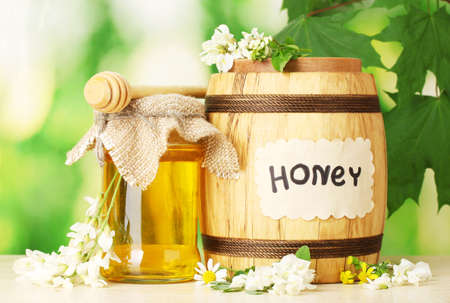Sweet honey in barrel and jar with acacia flowers on wooden table on green background photo