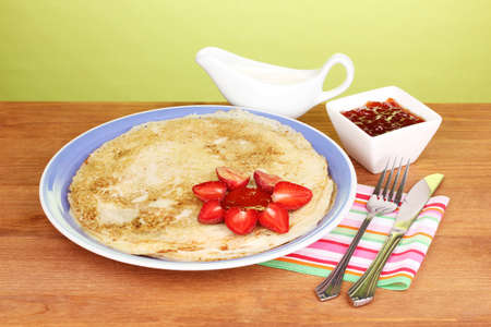 Stack of tasty pancakes on wooden table on green background photo