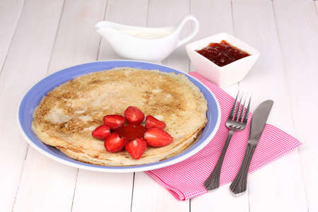 Stack of tasty pancakes on wooden background photo