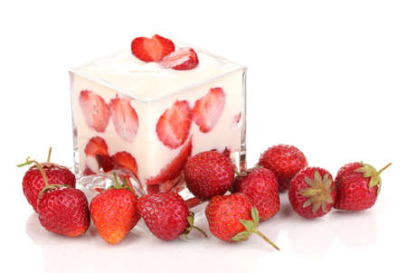 Glass of ripe strawberries with cream isolated on white photo