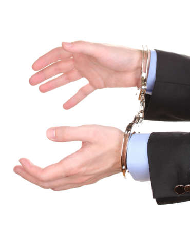 Businessman hands fettered with handcuffs isolated on white photo