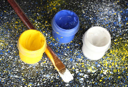 spattered: Jars with colorful gouache and brush on black background, spattered with colorful paint close-up