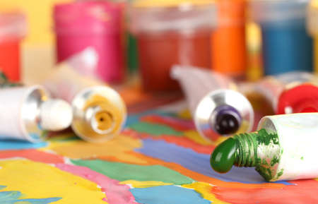 tubes with colorful watercolor and jars with gouache on colorful picture close-up photo