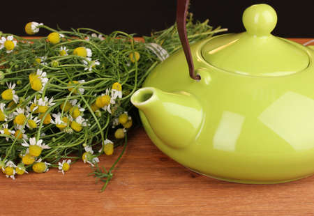 Teapot with chamomile tea on wooden table close-up photo