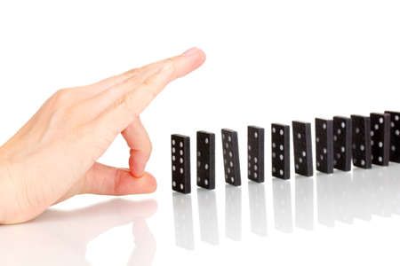 cause and effect: Hand pushing dominoes isolated on white