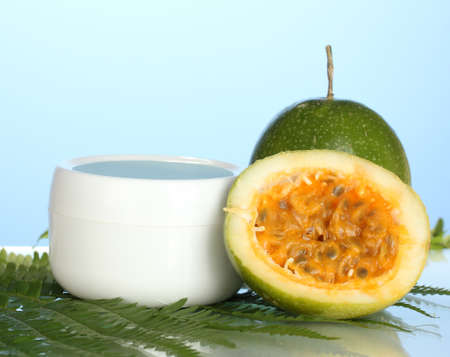 green passion fruit with cosmetical cream on blue background close-up photo