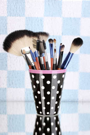 Makeup brushes in a black polka-dot cup on colorful background photo