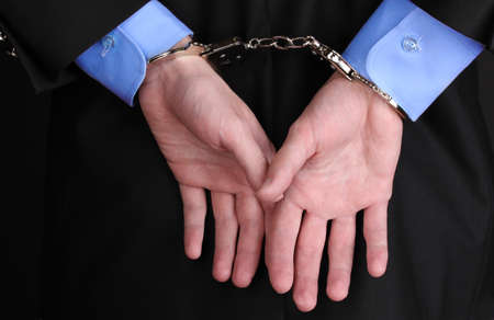 fettered: Businessman hands fettered with handcuffs