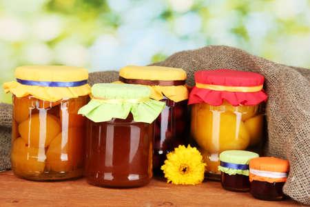 frutta sciroppata: Vasi con conserve di frutta su sfondo verde