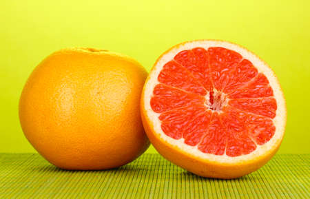 Ripe grapefruit and half on bamboo mat on green background Stock Photo - 14179690