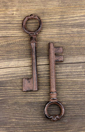 Two antique key on wooden background photo