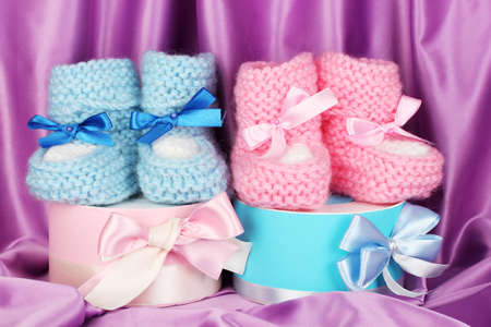 pink and blue baby boots and gifts on silk background  photo