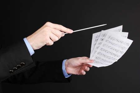 Música manos del conductor con bastón y notas aisladas en negro