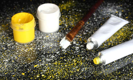spattered: Jars with white and yellow gouache, brush and tubes with white and yellow watercolor on black background, spattered with white and yellow paint close-up Stock Photo