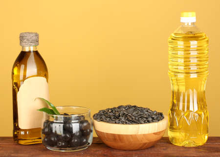 Olive and sunflower oil in the bottles on yellow background close-up photo