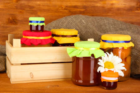 canned fruit: Jars with canned fruit on wooden background