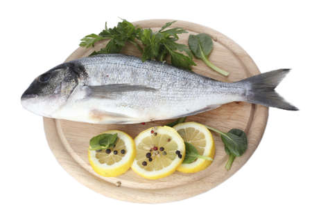 Fresh fish with lemon, parsley and spice on wooden cutting board isolated on white  photo