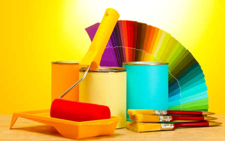 tin cans with paint, roller, brushes and bright palette of colors on wooden table on yellow background photo